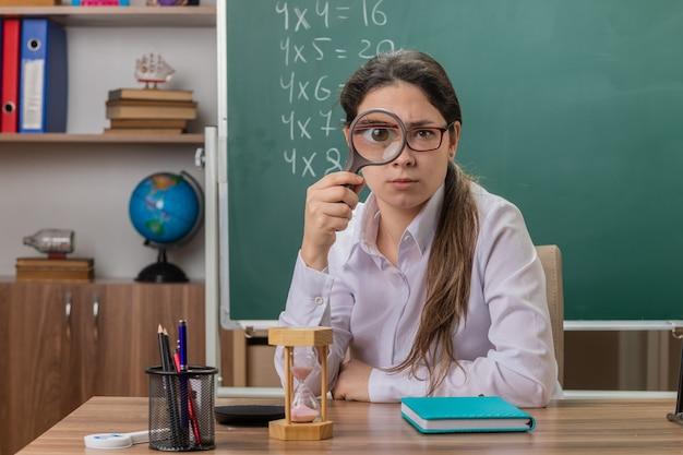 Młoda kobieta nauczyciel w okularach patrząc z przodu przez szkło powiększające siedzi przy ławce szkolnej przed tablicą w klasie
