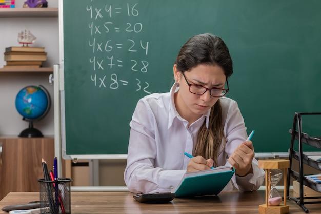 Młoda kobieta nauczyciel w okularach pisze coś w notesie przygotowując się do lekcji patrząc pewnie siedzi przy ławce szkolnej przed tablicą w klasie