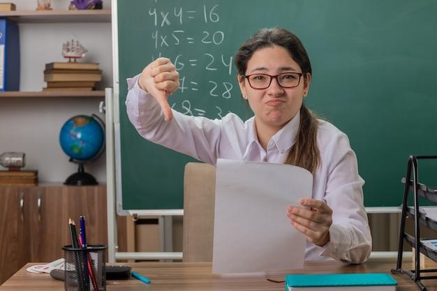 Młoda kobieta nauczyciel w okularach siedzi przy szkolnej ławce z pustymi stronami wyglądającymi na zdezorientowanego i niezadowolonego, pokazując kciuki w dół, sprawdzając prace domowe przed tablicą w klasie