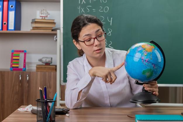 Młoda kobieta nauczyciel w okularach trzyma kulę ziemską wyjaśniając lekcję patrząc pewnie siedząc przy ławce szkolnej przed tablicą w klasie
