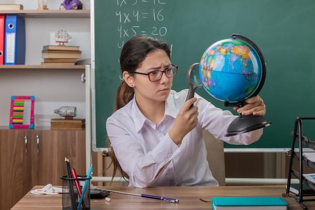 Młoda kobieta nauczyciel w okularach trzyma kulę ziemską