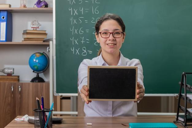 Młoda kobieta nauczyciel w okularach trzyma małą tablicę wyjaśniającą lekcję uśmiechnięty pewnie siedzi przy ławce szkolnej przed tablicą w klasie