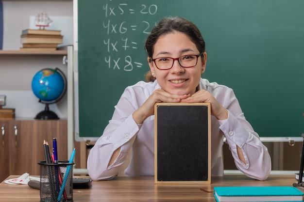 Młoda kobieta nauczyciel w okularach, trzymając małą tablicę wyjaśniającą lekcję patrząc na przód, uśmiechając się wesoło przy ławce szkolnej przed tablicą w klasie