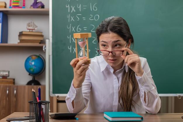 Młoda kobieta nauczyciel w okularach z klepsydrą patrząc na to