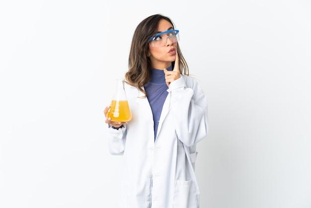Młoda kobieta naukowa na białym tle na białej ścianie, mając wątpliwości podczas wyszukiwania