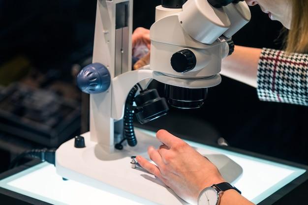 Młoda kobieta naukowiec patrząc przez mikroskop w laboratorium.