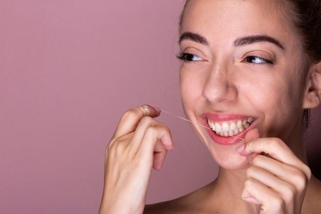 Młoda kobieta nicią dentystyczną zęby