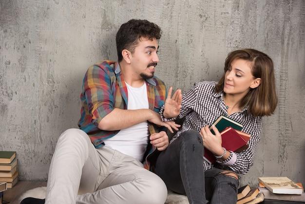 Młoda kobieta nie daje książek mężczyźnie