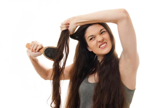 Młoda kobieta nie może rozczesać problematycznych splątanych włosów. na białym odosobnionym zakończeniu up