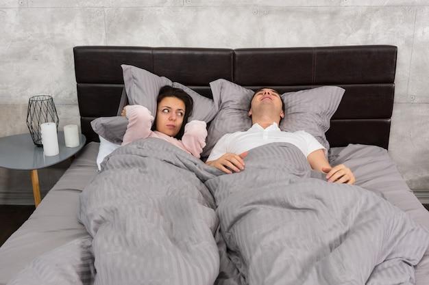 Młoda kobieta nie może spać i zakrywa uszy poduszką, ponieważ jej chłopak chrapie podczas snu w łóżku w sypialni w loftowym stylu w szarych kolorach