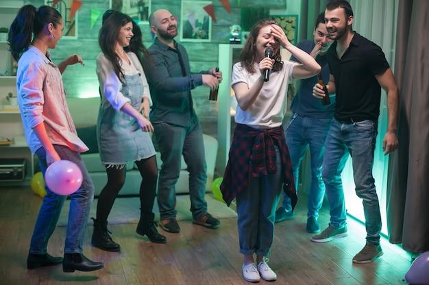 Młoda kobieta nie może uwierzyć, że robi karaoke na imprezie przyjaciół.