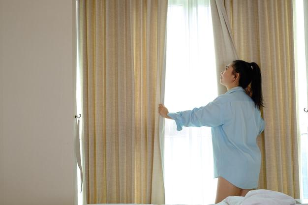Młoda kobieta nie nosi spodni, ciągnie otwierające zasłony w sypialni po przebudzeniu się rano
