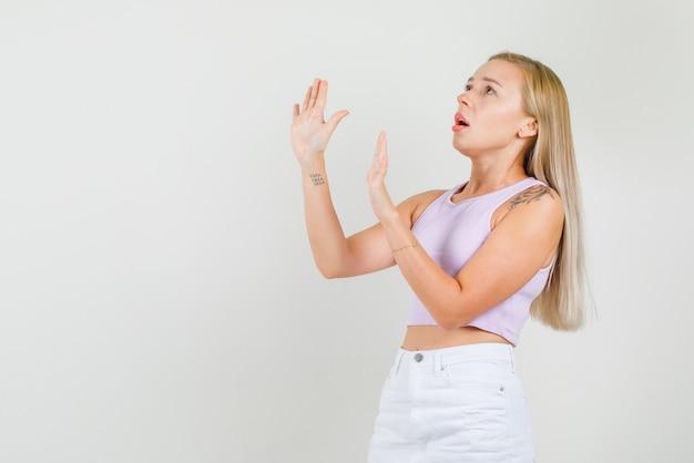 Młoda kobieta nie pokazuje gestu, patrząc w podkoszulek