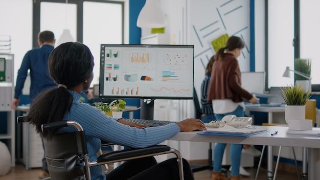 Młoda kobieta niepełnosprawna pracownica analizująca informacje statystyczne siedząca na wózku inwalidzkim przed komputerem, wpisująca projekt finansowy w startowym miejscu pracy