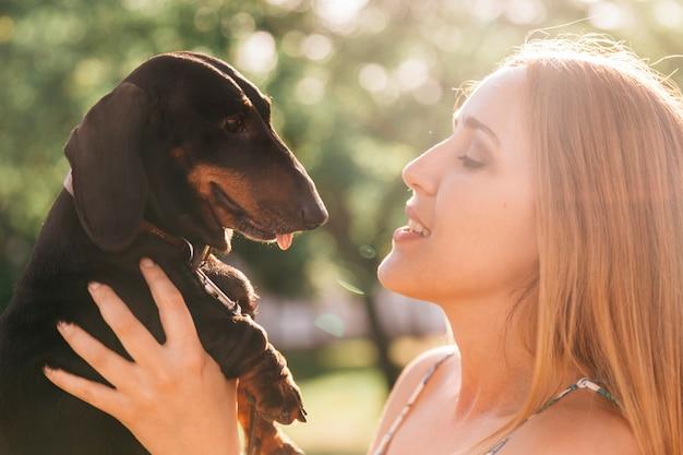 Młoda kobieta niesie jej psa w świetle słonecznym