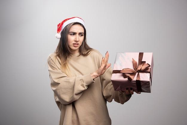 Młoda kobieta niezadowolona z prezentem bożonarodzeniowym.