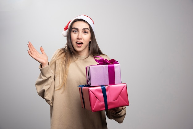Młoda kobieta niosąca dwa pudełka prezentów świątecznych.