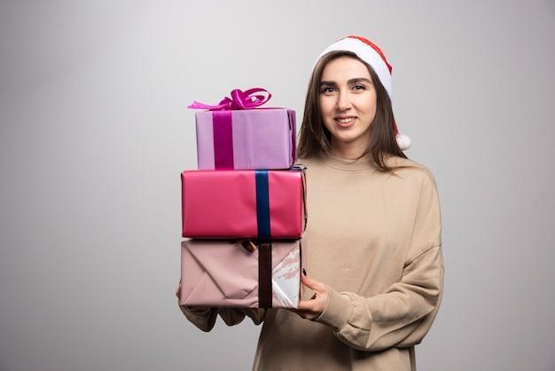 Młoda kobieta niosąca trzy pudełka prezentów świątecznych.