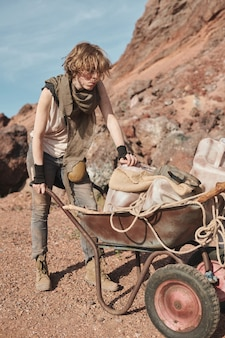 Młoda kobieta niosąca wózek z rzeczami na pustyni ucieka z kraju