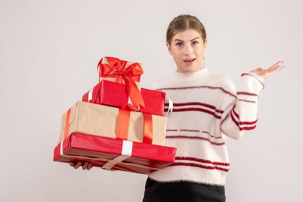 Młoda kobieta niosących boże narodzenie prezenty na białym tle