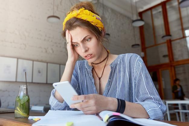 Młoda kobieta nosi chustkę i studiuje w kawiarni