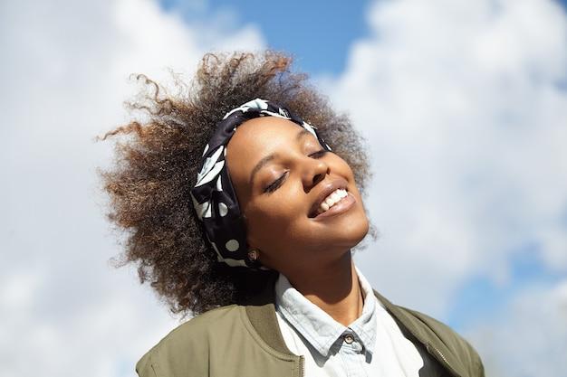 Młoda kobieta nosi chustkę z kręconymi włosami