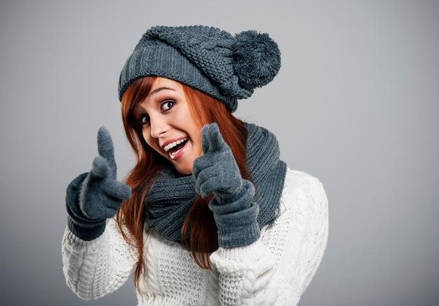 Młoda kobieta nosi ciepłe ubrania, wskazując na aparat