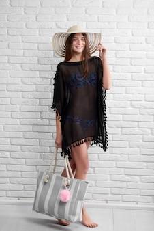 Młoda kobieta nosi czarne pareo i kapelusz, niosąc torbę