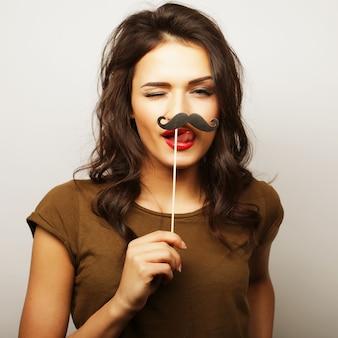 Młoda kobieta nosi fałszywe wąsy. gotowy na imprezę.