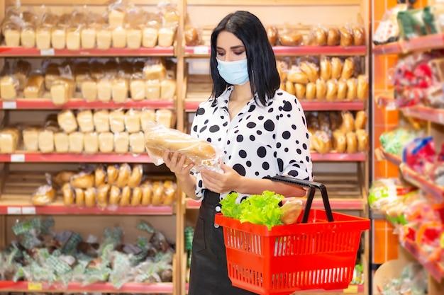 Młoda kobieta nosi jednorazową maskę medyczną zakupy w supermarkecie podczas wybuchu koronawirusowego zapalenia płuc. ochrona i środki zapobiegawcze w czasie epidemii.