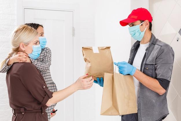 Młoda kobieta nosi maseczkę medyczną odbierania zamówionej żywności z restauracji od człowieka dostawy w pomieszczeniu. zapobieganie rozprzestrzenianiu się wirusa