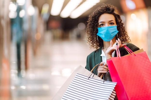 Młoda kobieta nosi maskę ochronną przed koronawirusem po zakupach.