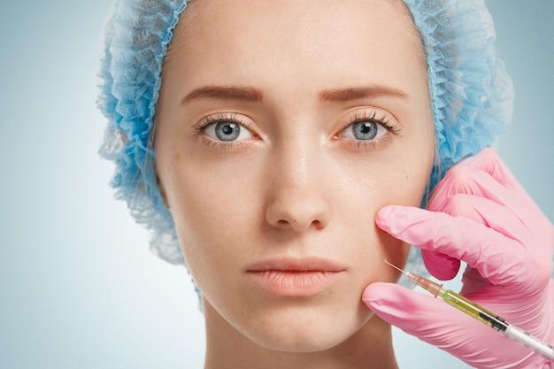 Młoda kobieta nosi medyczne nakrycia głowy, podczas gdy lekarz wstrzykuje jej twarz