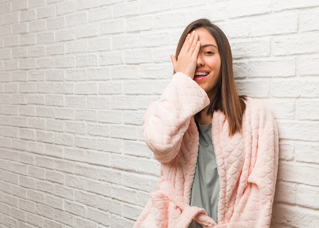 Młoda kobieta nosi piżamę krzycząc szczęśliwy i obejmujących twarz ręką
