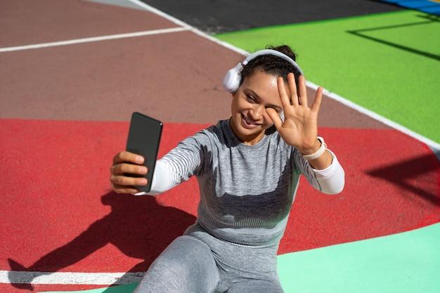 Młoda kobieta nosi słuchawki i bierze selfie ze smartfonem