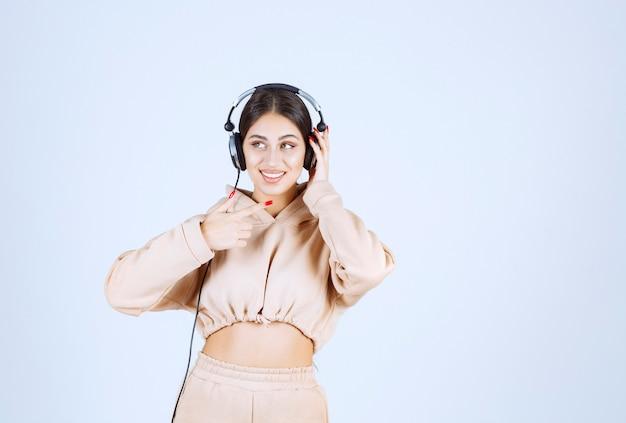 Młoda kobieta nosi słuchawki i słucha swojej listy odtwarzania z przyjemnością