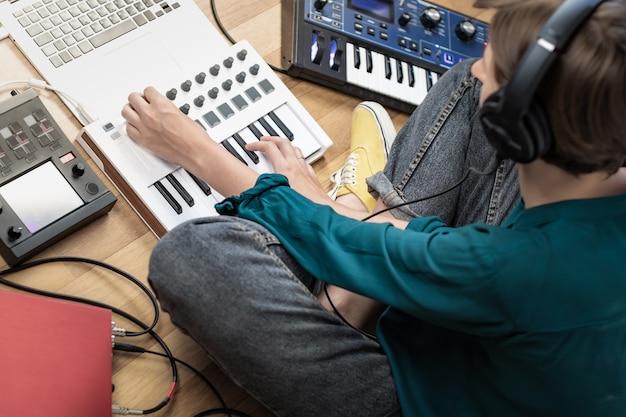 Młoda kobieta nosi słuchawki studyjne produkujące nowoczesną muzykę elektroniczną. żeński muzyk w domu studio z instrumentami, laptopem i procesorami efektów.