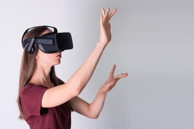Młoda kobieta nosi słuchawki wirtualnej rzeczywistości, pole vr. połączenie, technologia, nowa generacja, koncepcja postępu. dziewczyna próbuje dotykać obiektów w wirtualnej rzeczywistości. studio strzał w kolorze szarym
