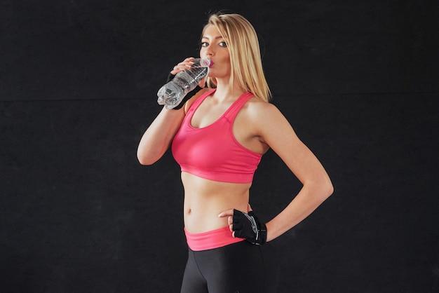 Młoda kobieta nosi sportowe ubrania i wody pitnej