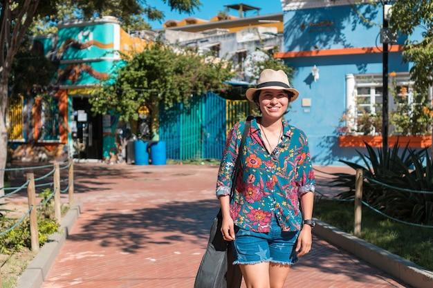 Młoda kobieta nosi torbę z gitarą, spacerując samotnie po parku