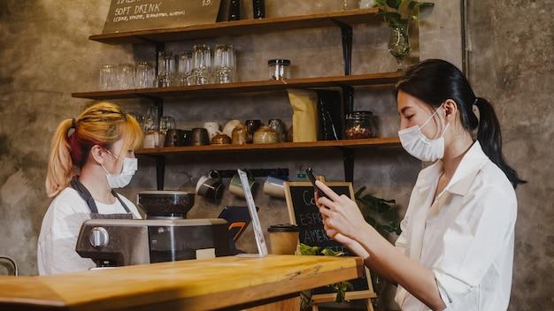 Młoda kobieta nosić maskę samoobsługową korzystać z telefonu komórkowego zapłacić zbliżeniowo w restauracji.