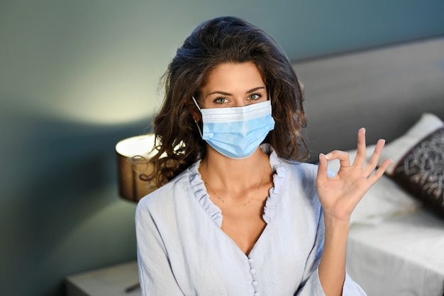 Młoda kobieta nosząca chirurgiczną maskę na twarz podczas pandemii koronawirusa wykonująca gest ok ręką w koncepcji nowego normalnego stylu życia