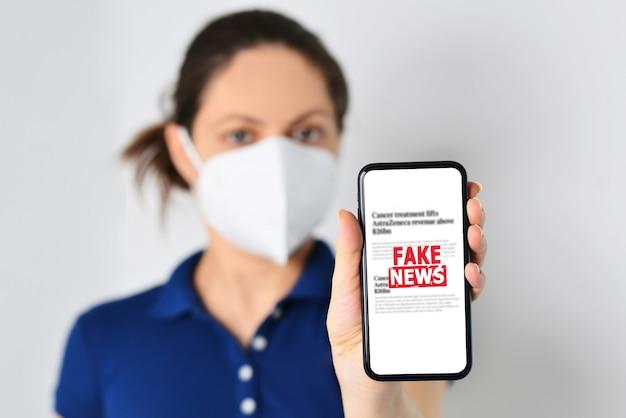 Młoda kobieta nosząca maskę medyczną i trzymająca smartfona z fałszywymi wiadomościami z przodu