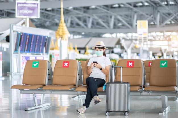 Młoda kobieta nosząca maskę na twarzy i korzystająca ze smartfona na lotnisku, ochrona przed zakażeniem koronawirusem (covid-19), azjatycka podróżniczka siedząca na krześle. nowa normalność i dystans społeczny