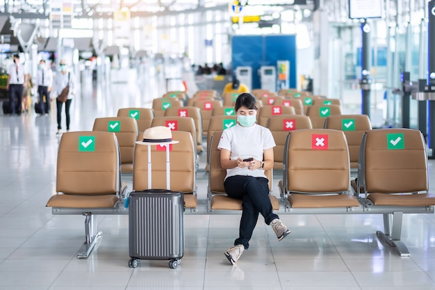 Młoda kobieta nosząca maskę na twarzy i korzystająca ze smartfona na lotnisku, ochrona przed zakażeniem koronawirusem (covid-19), azjatycka podróżniczka siedząca na krześle.