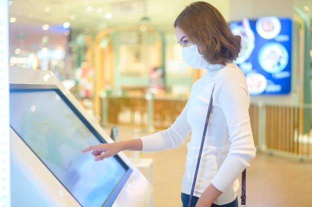 Młoda kobieta nosząca maskę ochronną w centrum handlowym, robiąca zakupy w ramach koncepcji pandemii covid-19.
