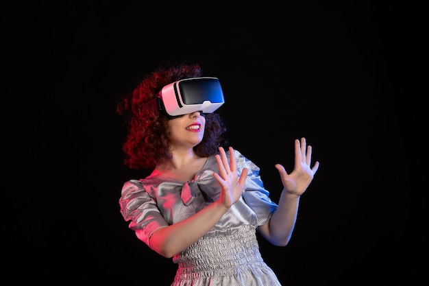 Młoda kobieta nosząca zestaw wirtualnej rzeczywistości na ciemnym biurku w technologii wizualnej wizji vision