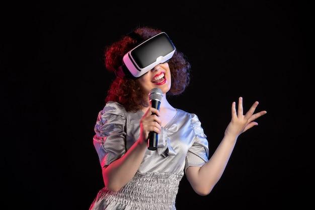 Młoda kobieta nosząca zestaw wirtualnej rzeczywistości z mikrofonem do gier wideo z muzyką