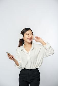 Młoda kobieta, noszenie słuchawek i słuchanie muzyki na smartfonie