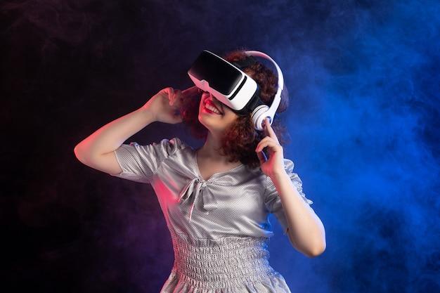 Młoda kobieta noszenie zestawu słuchawkowego vr w słuchawkach na ciemnoniebieskiej powierzchni